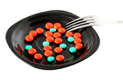 Tablets. Red and green tablets on a black plate stock photo