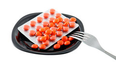 Tablets. Red tablets on a black plate stock image