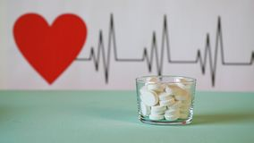 Tablets on the background of the cardiogram of the heart. Helthy heart  concept. Time laps