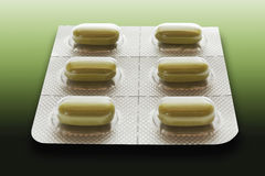 Tablets in blister pack on green background Royalty Free Stock Photography