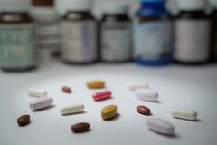 Tablets and capsule pills lay in front of blurry bottles on white background. Tablets, capsule pills and medicine bottles mean drug, pharmacy,healthcare and royalty free stock photography
