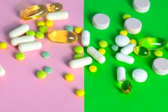 Tablets and capsules of different colors scattered. stock photo