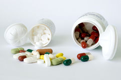 Tablets and capsules with two bottles. Different forms and colours tablets and capsules and two white bottles Stock Image