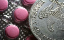 Tablets and coin. The box of pink tablets and one dollar coin (close-up background Royalty Free Stock Photos