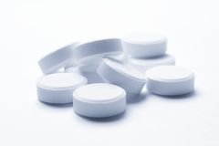 Tablets in cold tones. Blue round pills on surface Royalty Free Stock Photos