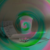 Tablets with the crucible covered with pink-and-green spiral. Tablets with the crucible and paper napkin covered with pink-and-green spiral Royalty Free Stock Images