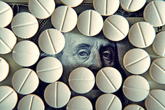 Tablets on dollar bills (treatment, addiction, aging - concept). Stock Photography