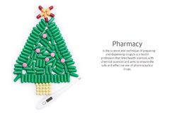 Tablets in form of Christmas tree and thermometer under it Royalty Free Stock Photo