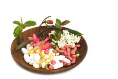 Tablets, pills, capsules & flowers. Wooden bowl with tablets, pills, capsules, vitamins and flowers Stock Photo