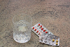 Tablets or pills and a glass of water. Stock Photography