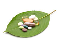 Tablets and pills on green leaf Stock Image