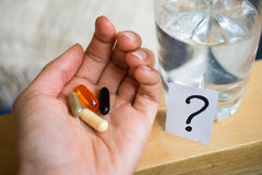 Tablets ,pills in hand near a glass of water and question mark Stock Photo
