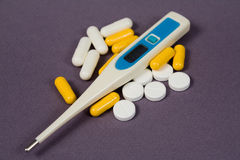 Tablets, pills and an thermometer Stock Photos