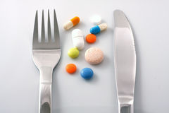 Tablets on plate with fork and knife Stock Image