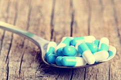 tablets Preventivpillerar på en träbakgrund apotek Medicin Full sked av tabletes Royaltyfri Fotografi