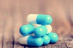 tablets Preventivpillerar på en träbakgrund apotek Medicin Full sked av tabletes Arkivbild