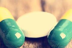 tablets Preventivpillerar på en träbakgrund apotek Medicin Full sked av tabletes Arkivbilder
