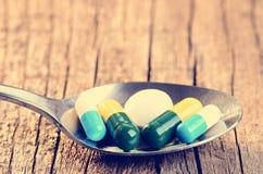 tablets Preventivpillerar på en träbakgrund apotek Medicin Full sked av tabletes Royaltyfri Bild