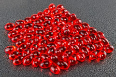 Tablets red capsules in bulk, with a depth of field picture Royalty Free Stock Photos