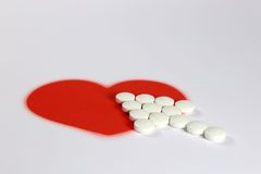 Tablets and a red heart. Arrow of white tablets with red hearts Stock Photo