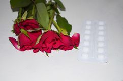 Tablets with roses flowers. Red roses flowers with film -coated tablets  on white Stock Images