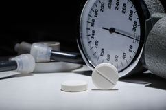 Tablets and a set for measuring pressure on a white table Royalty Free Stock Image
