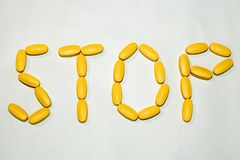 Tablets und Kapseln werden der Wort Halt ausgebreitet Lizenzfreie Stockfotos