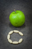 Tablets of Vitamin C and apple green. Royalty Free Stock Photos
