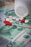 Tablets on Yuan banknotes (renminbi) for medication concept. Stock Photography