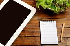 Tablette avec de la salade de carnet et de légume images stock