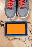Tablette avec des écouteurs et des espadrilles sur le fond en bois Photo stock