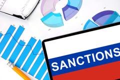 Tablette avec des sanctions de mot sur le drapeau russe Photographie stock