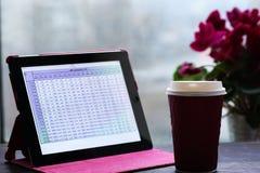 Tablette avec des tables, tasse de café par la fenêtre Photographie stock
