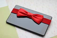 Tablette avec l'arc rouge, cadeau image stock