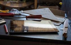 Tablette avec la réflexion sur un placard foncé avec des outils Photographie stock libre de droits