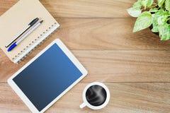 Tablette avec la tasse de café chaude, le pot de plante verte, le carnet et les stylos sur le bureau en bois Images libres de droits
