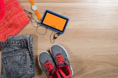 Tablette avec les écouteurs, la montre, l'habillement et les espadrilles sur le fond en bois Image stock