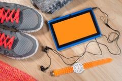 Tablette avec les écouteurs, la montre, l'habillement et les espadrilles sur le fond en bois Images stock