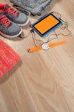 Tablette avec les écouteurs, la montre, l'habillement et les espadrilles sur le fond en bois Photographie stock