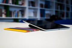 Tablette avec un écran vide et des crayons colorés sur le tabl de bureau Photo stock
