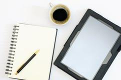 Tablette avec un bloc-notes et une tasse de café Photographie stock