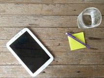 Tablette blanche avec un écran vide sur la table en bois, n Image stock