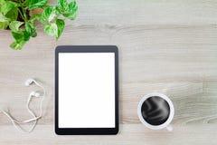 Tablette blanche vide d'écran avec la tasse de café, l'écouteur et le pot chauds de plante verte sur le bureau en bois Photos stock