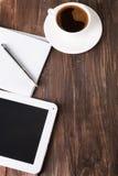 Tablette, carnet de papier et café sur la table Image libre de droits