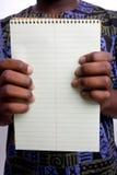 Tablette d'écriture de fixation d'homme de couleur Photo stock