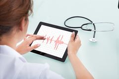 Tablette d'Analyzing Heartbeat On Digital de cardiologue Images libres de droits