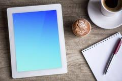 Tablette d'Ipad avec la tasse de café au-dessus de table en bois Images stock