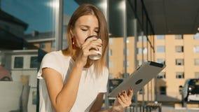 Tablette d'utilisations de fille pendant la pause-café banque de vidéos