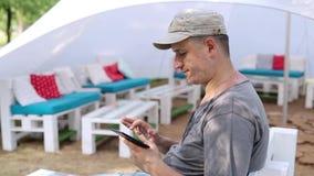 Tablette d'utilisations d'homme en parc banque de vidéos