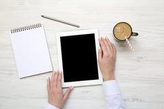 Tablette dans des mains femelles Espace de travail féminin avec le carnet et le lat Photographie stock libre de droits